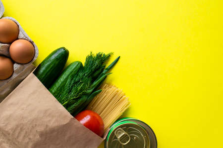 Healthy food delivery during coronavirus. Organic daily meal on yellow background with copy space. Eggs, vegetables, cucumbers, tomatoes, herbs, pasta, oil, canned food in paper bag package, top view. Фото со стока