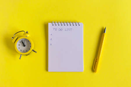 Notepad with text: to do list, clock and pen on a yellow background, spiral notebook on the table. Business, training education. Monochrome yellow and minimalism. Flatlay top view. Standard-Bild