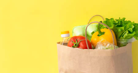 Healthy food delivery during coronavirus. Food donation on yellow background in paper bag package. Help cardboard box wiht various canned food, cereals, pasta and vegetables. Volunteer box. Copy space