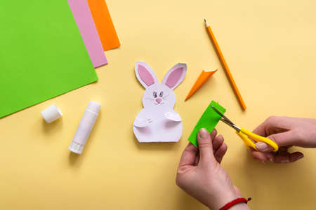 Step by step photo instruction How to make Origami paper bunny with carrot for Easter greetings card. Children's art project. DIY concept. Step 18