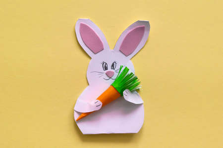 Step by step photo instruction How to make Origami paper bunny with carrot for Easter greetings card. Children's art project. DIY concept. with copy space