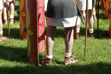 Legs of a Roman soldier with spear and shield, back view