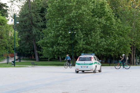 Milan, Italy - May 4, 2020: people exercising bicycling outdoor wearing face mask. Police patrol in central Sempione park. Italy eases coronavirus movement restrictions after two month lockdown