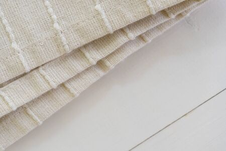 Kitchen towel on white rustic background. Dishtowel on wooden surface with copy space. Closeup of checked linen tablecloth for picnic. Beige serviette in restaurant