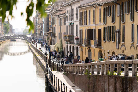 Milan, Italy - May 8, 2020: People walk in Naviglio Grande canal street wearing face mask. Police car keeps order. Second phase of quarantine in Europe. Concept of lockdown, flatten the curve Editorial