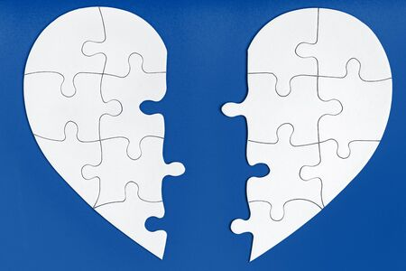 Two matching halves of one heart on trendy blue. Care, health, support, love concept. Separation, divorce, broken heart, break up. Perfect match, reunion. Finding love partner. Jigsaw puzzle