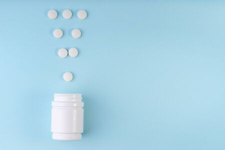 Exclamation point sign, mark from pharmaceutical medicine pills. Creative layout of tablets and bottle on blue. Exclamation symbol. Medicine, healthcare concept. Copy space, flat lay Banque d'images