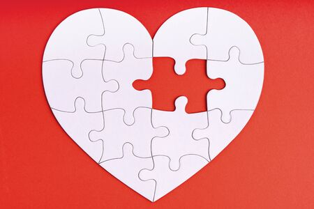 Love, charity, donation, helping concept. Missing piece of jigsaw puzzle in heart shape on red. Looking for love partner. Uncompleted puzzle. Relationship. Mental health problems, heartache