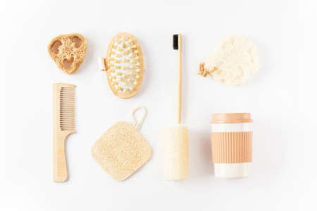 Reusable eco friendly items on white surface. Bamboo toothbrush, detangling hair brush, coffee mug, exfoliating loofah sponge, massaging brush. Sustainable lifestyle. Zero waste, plastic free concept