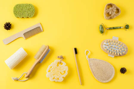 Jade face roller, anti cellulite massager, loofah and bamboo sponges, hairbrush, wooden comb on yellow surface. Tools for beauty routine from ecological material. Zero waste bath. Copy space, flat lay