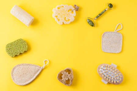 Jade face roller, anti cellulite massager, loofah and bamboo sponges on yellow surface. Frame from tools for beauty routine from ecological material. Zero waste bathroom. Copy space, flat lay