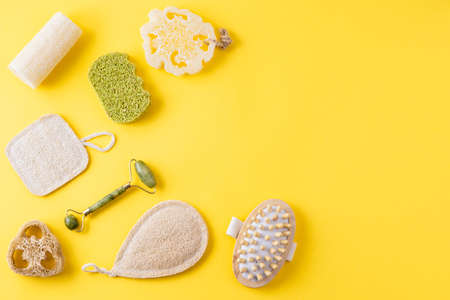 Tools for beauty routine from ecological material. Zero waste bathroom. Jade face roller, anti cellulite massager, loofah and bamboo sponges on yellow surface. Copy space, flat lay Imagens
