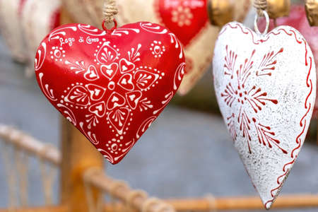Souvenir heart. Traditional alpine cow bells in the shape of heart on street market. Text on heart means Lake Como