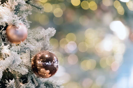 Decorated artificial christmas tree on soft blurred golden lights. Baubles on tree branch. Happy new year or merry christmas card. Festive holiday background. Banner, copy space
