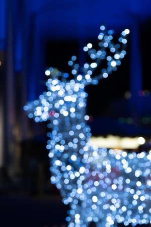 Blurred lights of christmas installation - defocused lights of deer on night city background. Christmas deer installation in Milan, Italy.