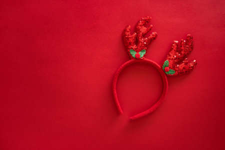 Christmas deer antlers in hipster style on red surface. Colorful reindeer antlers headband. Holiday costume detail. Copy space, top view