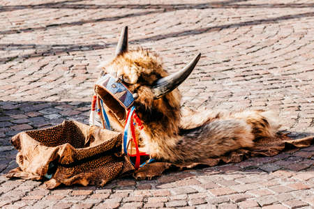 Headdress in american style with horns. Part of traditional costume lying on the ground with box for money. Street musicians headdress. Native American traditional Indian musicians hat Stock fotó