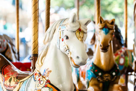 Vintage french carousel horse closeup in fair park. Merry-go-round horses in amusement fun park for children. Flying toy wooden animals in entertainment park