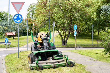 Lawn mower on grass on city park. Summer works in european cities. Professional lawnmower machine for cutting lawns, to cut grass outdoor. Keeping green enviroment in town