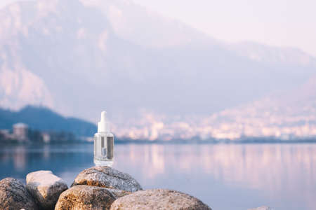 Hyaluronic acid, serum skincare glass bottle on stone, mountain lake background. Serum product cosmetic with peptide and collagen. Modern brand cosmetics packaging with shadow. Cosmetic showcase
