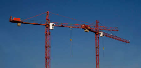 Two red crane on the blue sky