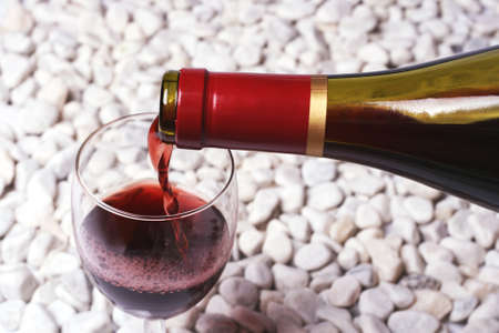 Red wine on the white stone. Stock Photo