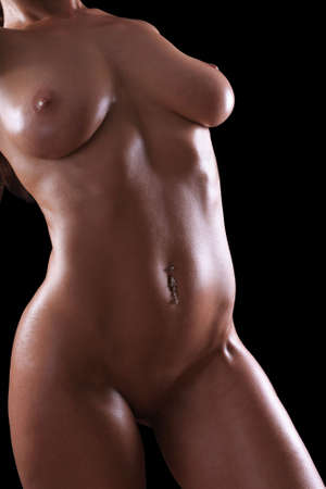 Low key nude female body with black background. Stock Photo