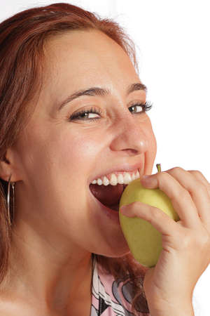 The cheerful young girl is eating a fresh green apple, knowing the saying  Stock Photo