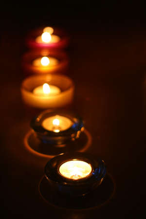 Some of candle on the table on black background in a glass holder. Stock Photo - 3472596