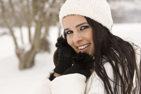 Smileing woman in snow with hands on face