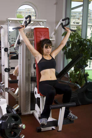 Young girl is doing exercises in a fitness room  gym