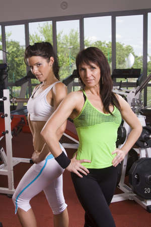 two fitness ladies, mother and daughter, posing at the gym