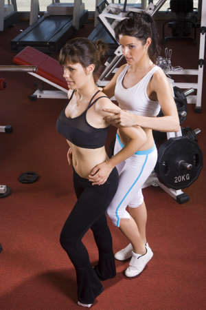 the coach helps young girl posing in the gym