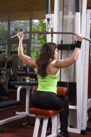 Muscular woman is doing exercises in a fitness room  gym photo