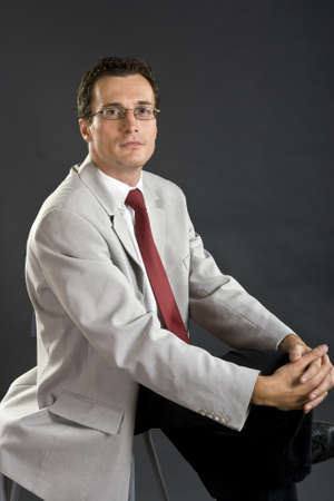 Man in grey jacket with red tie and glasses