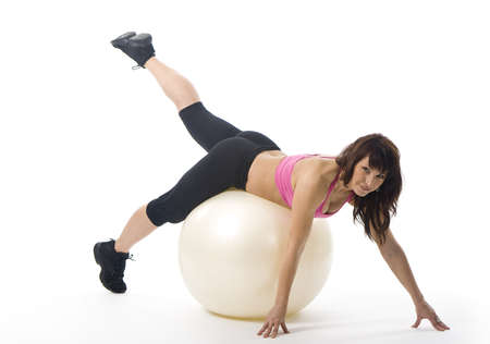 An attractive middle aged woman in sportswear with a fitball