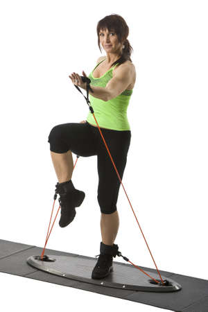 middle aged woman doing exercises with fitness equipment Stock Photo