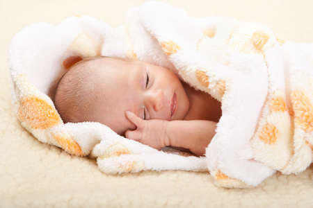 Baby lying on a soft blanket and holding his head. Stock Photo - 10685574