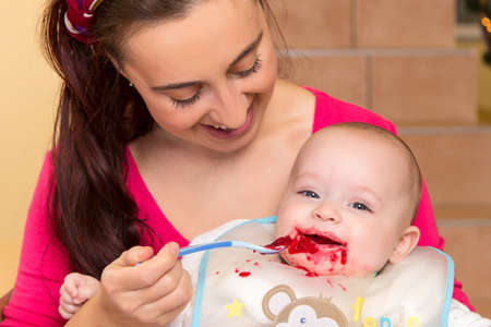 snotty: Mother is spoon feeding her snotty half year old son with beetroot puree
