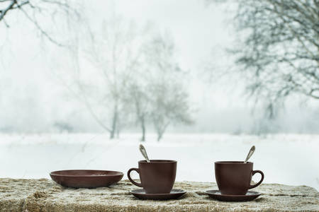 Two cups of tea on background of a winter landscape, outdoors Stock Photo