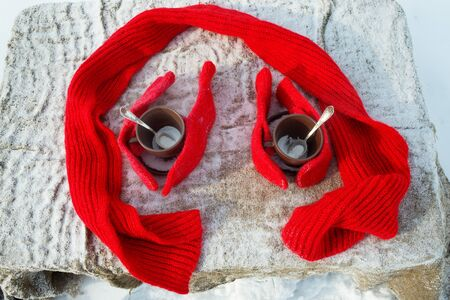 Two cups of tea with knitted gloves and a scarf on winter landscape Stock Photo