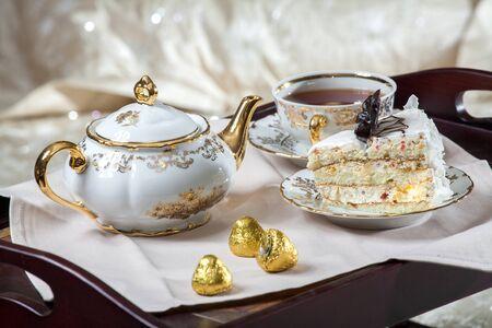 desayuno romantico: table on the bed with chocolates and tea Foto de archivo