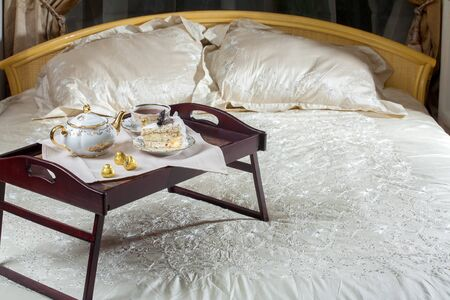 bed linen: table on the bed with chocolates and tea Stock Photo