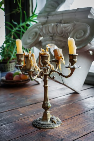greek column: Old candlestick with candles and greek column