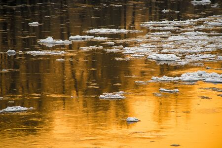 afloat: Melting snow on the water at sunset Stock Photo