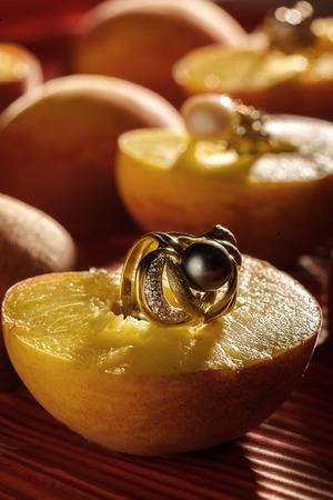 ear rings: a lot of earrings on sliced peaches