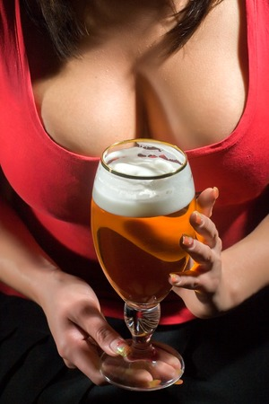 Woman with sexy bust in red t-shirt holding glass of beer