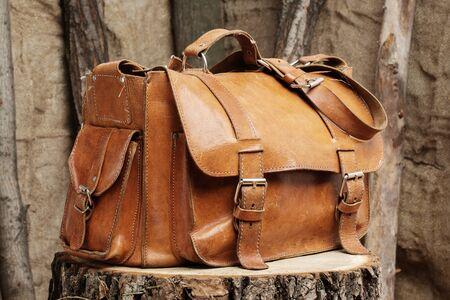mochila de viaje: bolso de cuero de la vendimia en un tocón de árbol Foto de archivo
