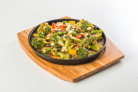 ragout: Vegetable ragout in pan on wooden board on white background