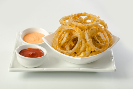 sauces: Onion rings and dip sauces on white plate